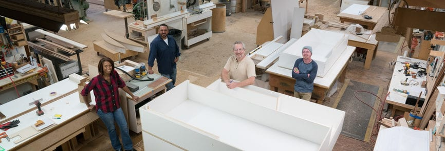 Elevated portrait of a proud team of carpenters in a cabinet shop